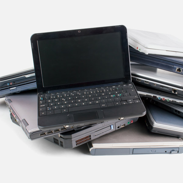 stack of old laptops for recycling